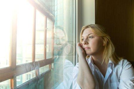Photo pour La femme perdu dans ses pensées, regardant par la fenêtre. matinée ensoleillée. - image libre de droit