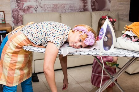 Photo for Woman tired ironed clothes and lay down on the ironing board - Royalty Free Image