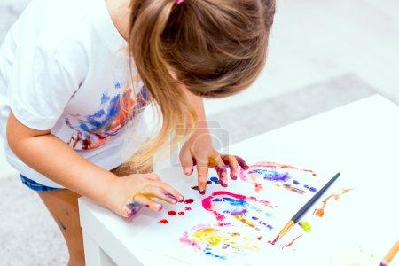 Little beautiful girl draws paints.