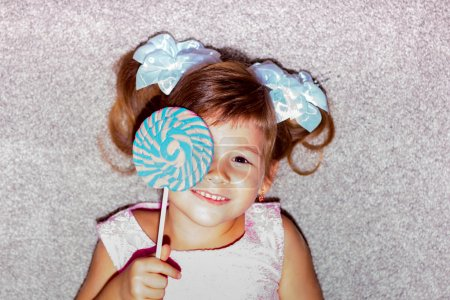 Little girl lying on the floor and holding a lollipop.