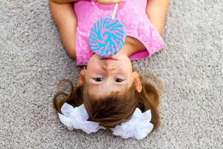 Little girl lying on the floor. Looking at the camera.