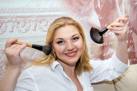 Photo pour Beau modèle d'âge moyen tenant des pinceaux de maquillage. pin-up de maquillage professionnel . - image libre de droit