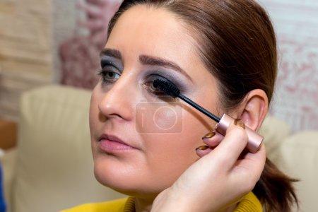 Photo pour Beau modèle d'âge moyen, qui est appliqué mascara. Maquilleur au travail . - image libre de droit