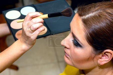 Photo pour Beau modèle d'âge moyen, qui est appliqué maquillage. Maquilleur au travail . - image libre de droit