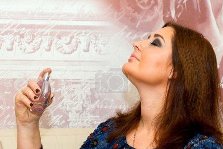 Photo pour Belle femme d'âge moyen applique parfum, maquillage professionnel . - image libre de droit