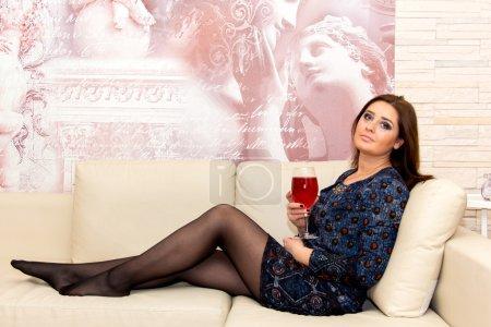 Photo pour Belle femme d'âge moyen assise sur le canapé avec un verre de vin, maquillage professionnel . - image libre de droit
