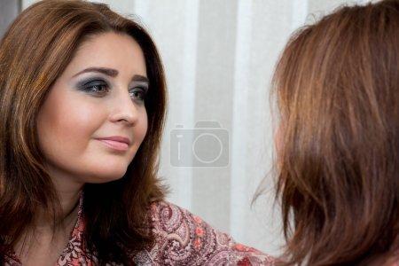 Photo pour Belle femme d'âge moyen se regardant dans le miroir et souriant . - image libre de droit