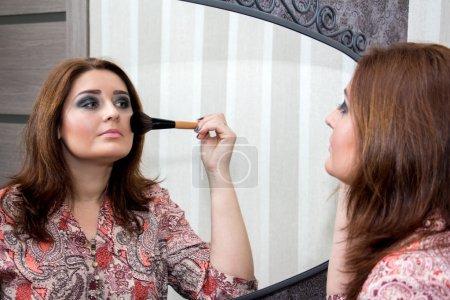 Photo pour Femme regardant dans le miroir et s'applique rougir. Focus sélectif sur la réflexion . - image libre de droit