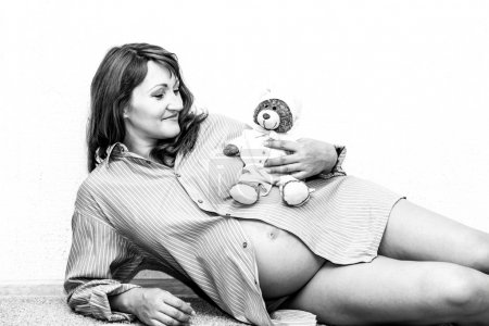Happy pregnant woman lying on the floor.