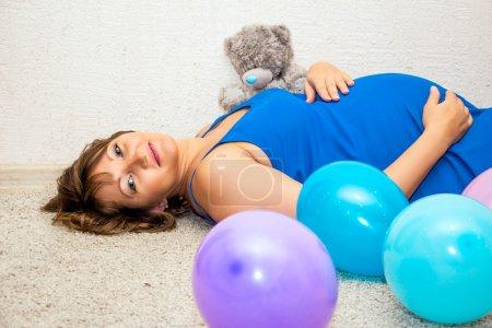 Photo pour Femme enceinte couchée sur le sol avec des ballons et un ours en peluche . - image libre de droit