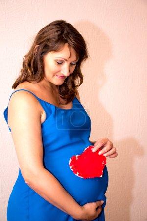 Photo pour Une femme enceinte tenant un cœur devant son ventre. Intérieur intérieur . - image libre de droit