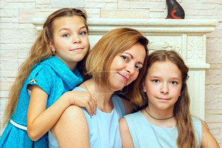 Photo pour Mère et ses deux filles assises près de la cheminée. Portrait de famille . - image libre de droit