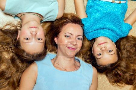 Photo pour Mère et ses deux filles couchées sur le sol. Portrait de famille . - image libre de droit