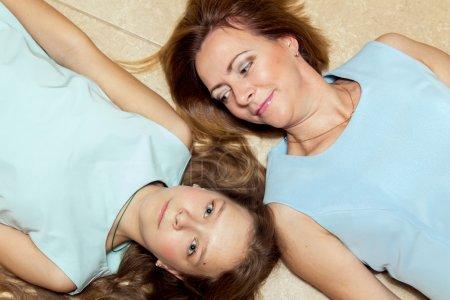 Photo pour Mère et fille couchées sur le sol, mère regardant sa fille . - image libre de droit