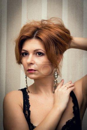 Photo pour Portrait d'une belle femme dans un négligé, qui se regarde dans le miroir . - image libre de droit