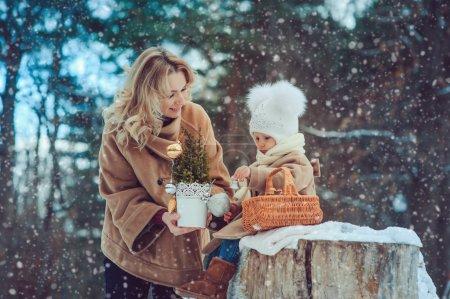 Photo pour Bonne mère et bébé fille marchant dans un parc d'hiver enneigé. Noël en famille . - image libre de droit