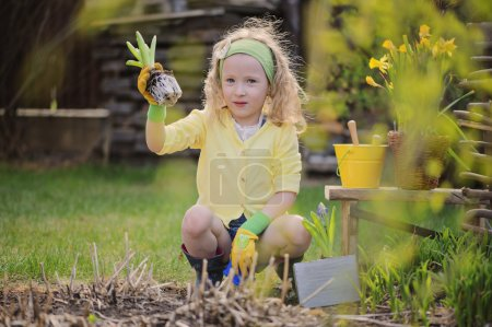 Cute happy child girl in yellow cardigan plays little gardener in spring garden