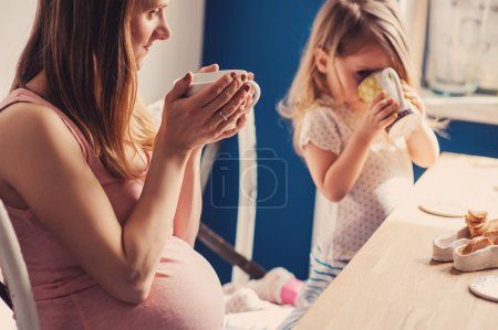 Happy loving pregnant mother and toddler daughter having breakfast and drinking tea at home