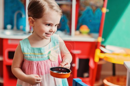 Photo for Happy   girl playing with toy kitchen at home. Cozy mood, lifestyle capture. - Royalty Free Image