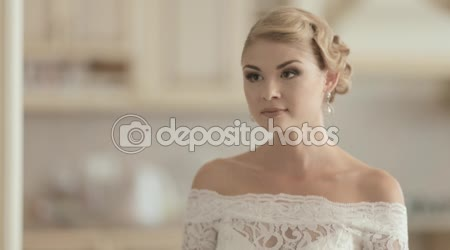 Young bride in a lace wedding dress laughing at home