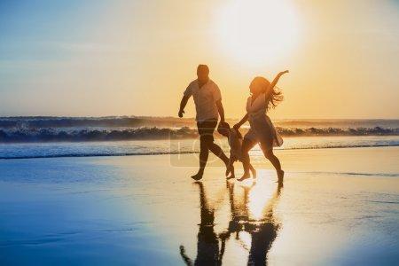 Photo pour Héhé - père, mère, fils de bébé tiennent par la main et courir avec plaisir le long du bord de mer coucher de soleil sur la plage de sable noir. Activités de plein air parents et personnes actives sur tropical vacances avec enfants - image libre de droit