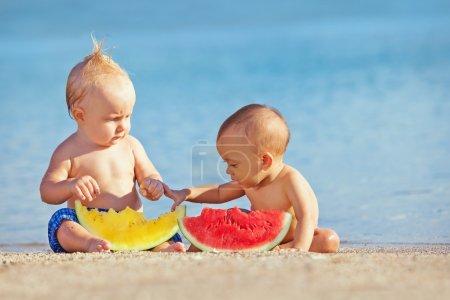 Foto de Después de retozar de natación mar asiático bebé niña y niño blanco divertirse y comen frutas en la playa de arena. Niños saludables alimentos, estilo de vida activo, actividad de agua y los niños viajan con los padres de familia vacatio - Imagen libre de derechos