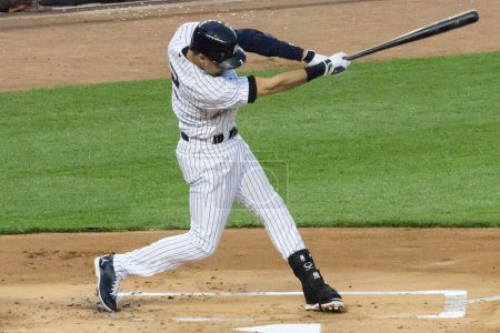 Photo pour Derek Jeter connects on a line drive to center field in his final season as a NY Yankee at Yankee stadium during the summer of 2014 - image libre de droit