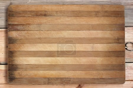 Photo for Chopping board in a strip on a wooden table. A blank space for your text. - Royalty Free Image