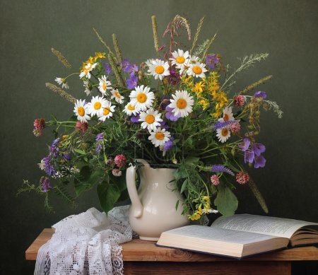 Photo for Still life with a summer bouquet of wild flowers and the opened book - Royalty Free Image