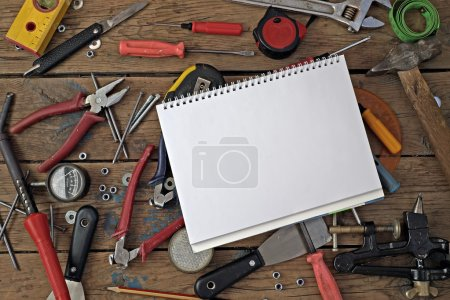 Photo for Tools on a timber floor, the top view. Tools are spread out round a notebook for records. A place for your text. - Royalty Free Image