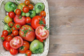 Fresh red and green tomatoes in a basket on a table