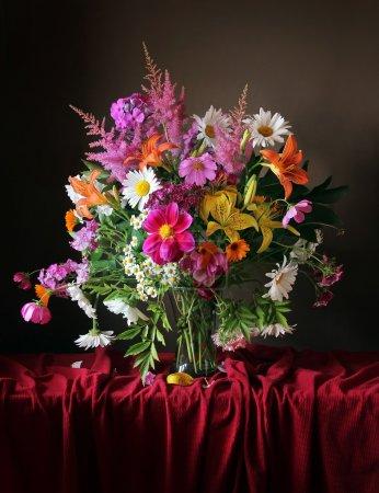 Photo pour Beau bouquet de fleurs cultivées dans un vase transparent sur un tissu rouge avec des plis - image libre de droit