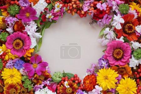 Photo pour Fond de fleurs. Un fond de fleurs cultivées et des baies avec un espace vide dans un tsenrta pour votre texte, la vue de dessus. - image libre de droit