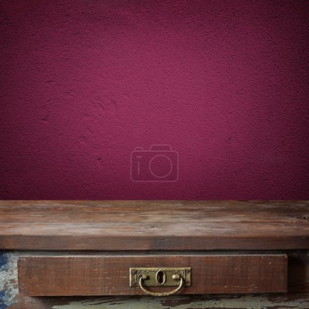 Empty wooden table against a violet wall.