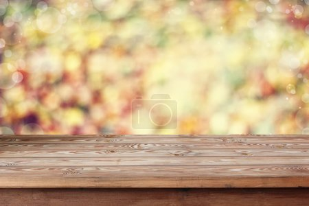 Empty wooden table on an indistinct background with a side.