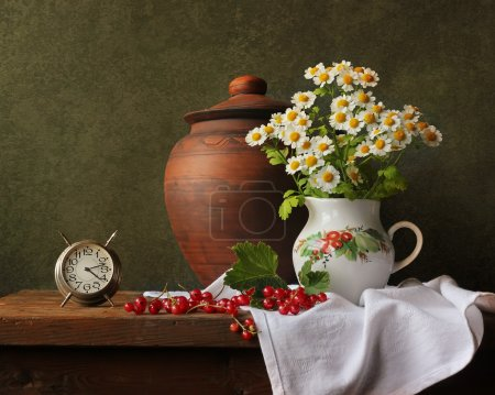 Photo for Still life with an alarm clock, camomiles and red currant. Summer still life. - Royalty Free Image