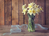 Still life with narcissuses in a glass jar