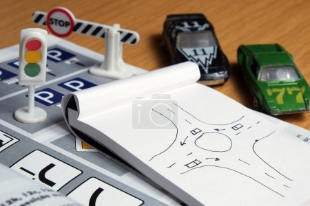 Photo for Notepad, book of traffic rules, toy cars, traffic lights and stop sign on a desk table. Studying and preparing for driving test - Royalty Free Image