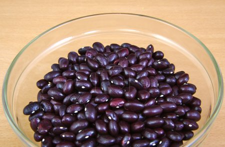 Uncoocked red beans in a cristal bowl on wooden ba...