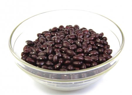 Top view of uncoocked red beans on wooden spoon. G...