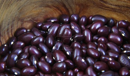 Closeup view of uncoocked red beans in a olive woo...