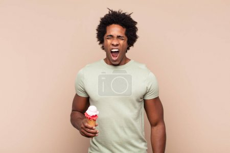 Photo for Young black afro man shouting aggressively, looking very angry, frustrated, outraged or annoyed, screaming no - Royalty Free Image