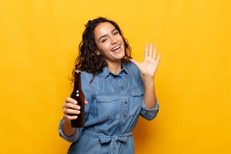 Photo for Young hispanic woman smiling happily and cheerfully, waving hand, welcoming and greeting you, or saying goodbye - Royalty Free Image