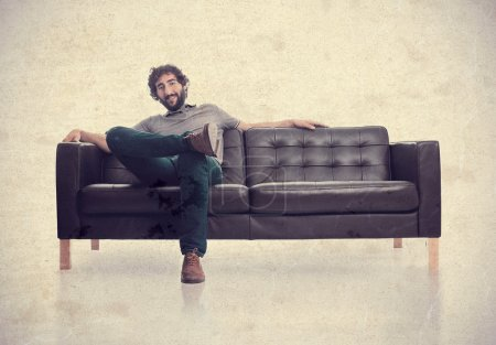 Young satisfied man in a sofa