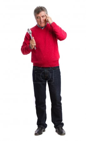 Thoughtful man holding a wrench