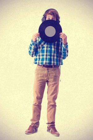 teenager with headphones holding a vinyl