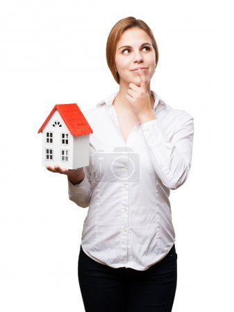 blond woman with a small house thinking