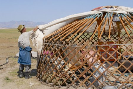 Photo for CIRCA HARHORIN, MONGOLIA - AUGUST 25, 2006: Unidentified Mongolian men assemble yurt (ger or nomadic tent) in steppe on August 25, 2006 circa Harhorin, Mongolia. The wooden frame of a yurt (ger) is covered with pieces of felt, depending on availabili - Royalty Free Image
