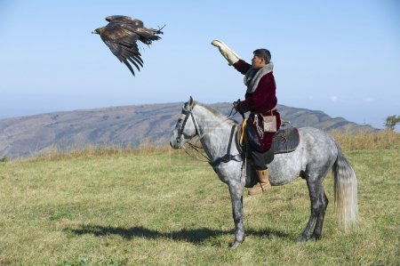 Mongolian hunter launches golden eagle to pursue prey circa Almaty, Kazakhstan.