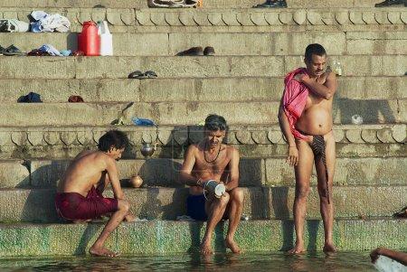 Pilgrims bathe in Holy Ganges river at sunrise in Varanasi, India.
